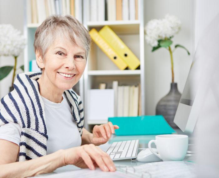 Zufriedene Seniorin arbeitet im Büro