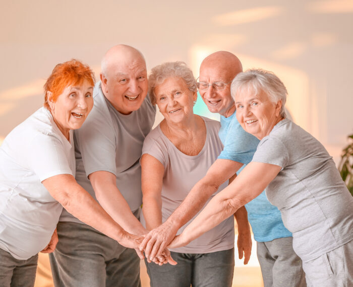 Happy,Elderly,People,Putting,Hands,Together,In,Gym